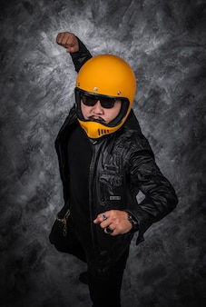 Biker man in motorcycle helmet and black leather jacket