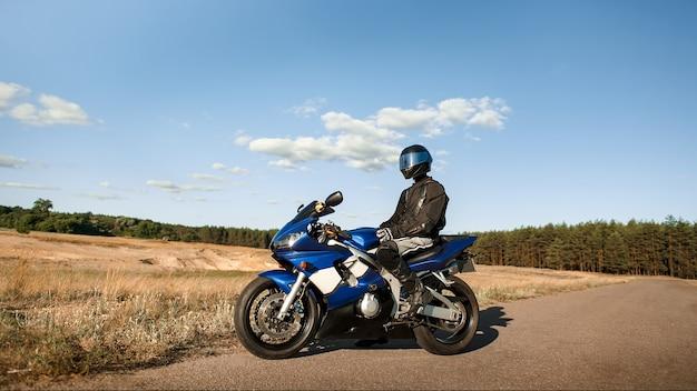 Байкер на мотоцикле в кожаной куртке и шлеме смотрит на дорогу