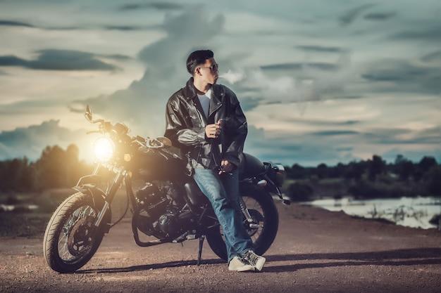 Байкер человек, стоящий курит на своем мотоцикле рядом с природным озером и красивым.