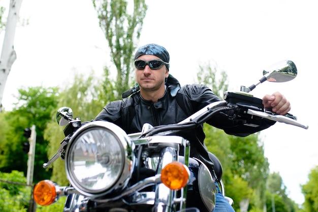 Байкер мужчина в очках на мотоцикле.