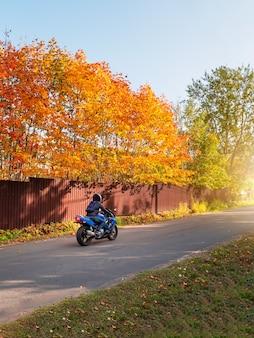 田舎の秋の道を走る青いバイクに乗ったバイカー。