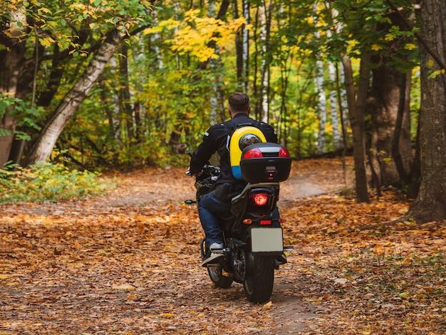 Байкер на мотоцикле едет по лесной дороге с собакой в рюкзаке на спине.