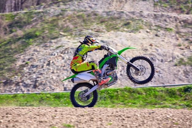 Байкер на мотоциклетных трюках при движении на заднем колесе, вид сбоку