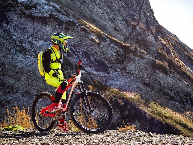 바위 배경에서 내리막 경주를 위해 산악 자전거를 타는 바이커