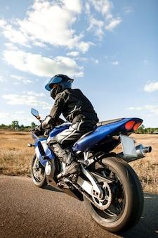 Байкер или мотоциклист в черном кожаном костюме и шлеме сидит на спортивном мотоцикле и смотрит вдаль.