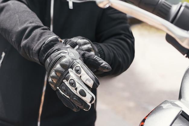 Байкер надевает перчатки, чтобы сесть на велосипед