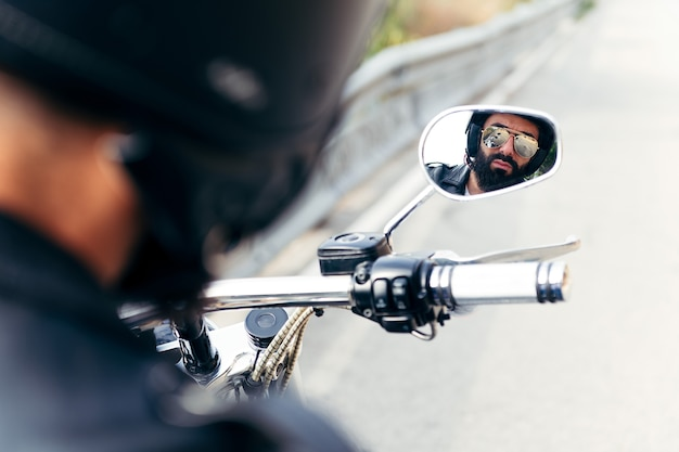 Biker reflected in the mirror of his motorcycle