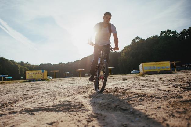 Байкер езда по пляжу на закате