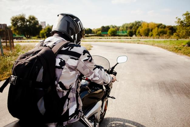 慎重に道路に乗るバイカー Premium写真