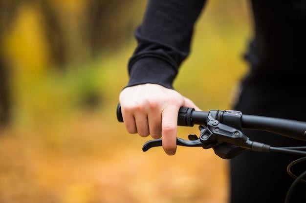 La mano del motociclista sul manubrio mentre guida nella fine del parco di autunno su