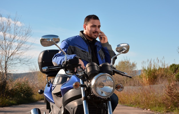 Biker talking by phone with his smarth phone