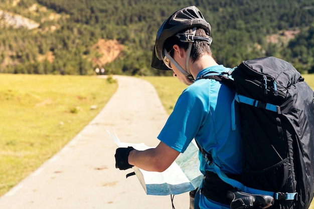 지도에서 그의 경로를 컨설팅하는 배낭과 자전거