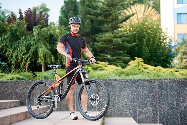Байкер с велосипедом на лестнице