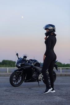 검은 가죽 자 켓 및 전체 얼굴 헬멧에 자전거 타는 여자 도시 주차장에서 세련 된 스포츠 오토바이 근처에 앉는 다. 여행과 활동적인 라이프 스타일 개념.