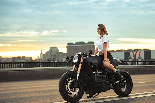 Байкер женщина, сидящая на винтажном пользовательском мотоцикле на открытом воздухе портрет образа жизни