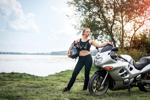 Biker woman with motorcycle rest near a pond