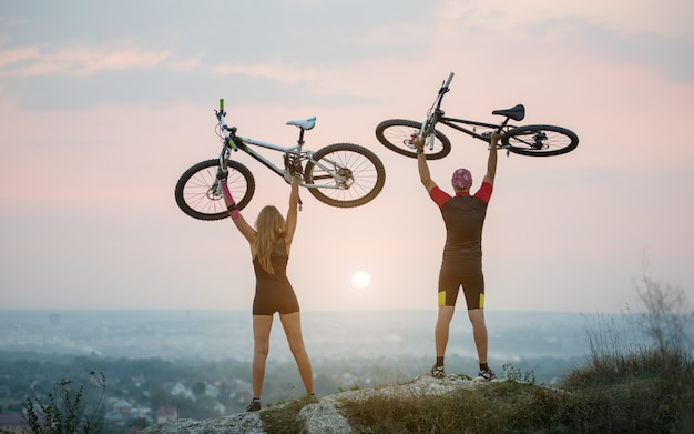 Bikers holding bikes high up in the sky on the top of a hill against magnificent sunset with blurred background. pink kinesio tape glued on the girl's hand.