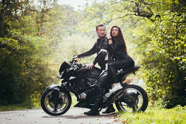 Байкеры в кожаной одежде, мужчина и женщина, сидящие на черном спортивном мотоцикле в лесу
