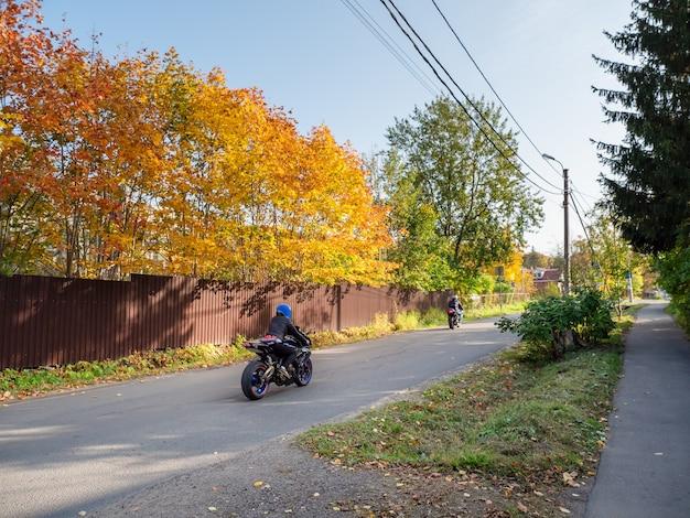 オートバイのバイカーは田舎の秋の道に乗る