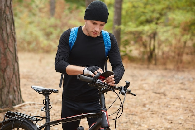Bikers using smart phone gps application to find right way in forest, attractive guy stops on road in wood, rider wears black sportwear and blue backpack spending free time in open air. sport concept.