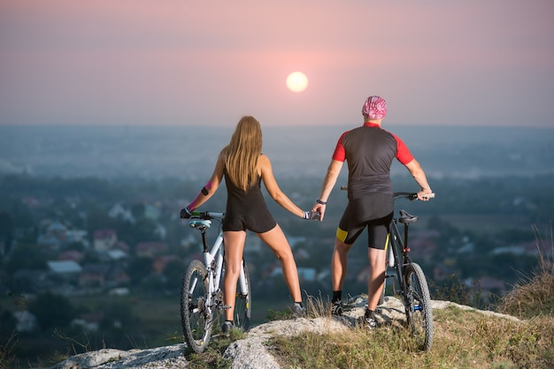 Bikers with mountain bicycles on the top of a hill at sunset