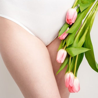 白い背景の上のピンクのチューリップと白い下着を着ている若い女性のビキニエリア