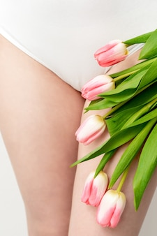 Bikini area of a young woman wearing a white underwear with pink tulips on white background
