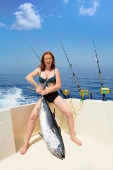 Bikini fisher woman holding bluefin tuna on boat