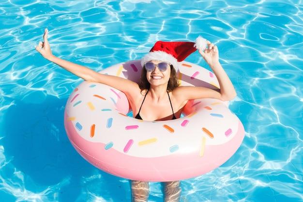 선글라스와 함께 크리스마스 모자에 비키니 소녀 핑크 풍선 수영장 반지에 편안합니다.