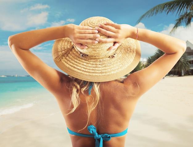 ビーチで帽子をかぶったビキニの女の子