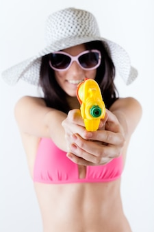 Bikini girl with squirt gun looking at camera