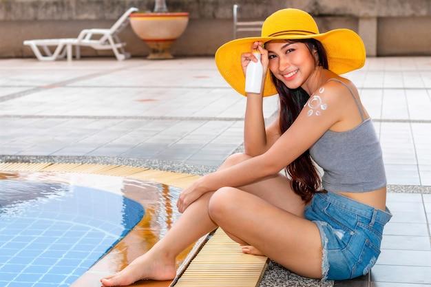 어깨에 보습 자외선 차단제 로션을 적용 비키니 모자 여자.