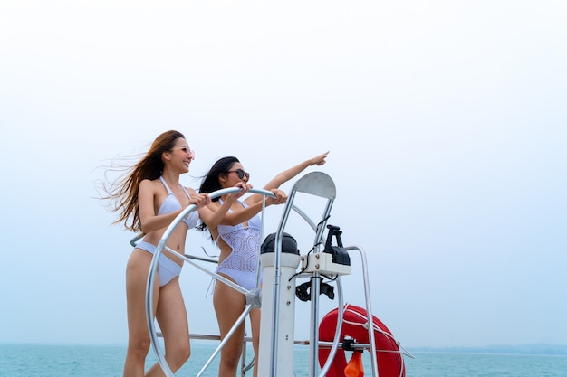 Bikini sexy girl stand and dance with driver hand steering wheel on boat yacht with background of sea and sky