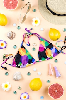 Bikini swimsuit with straw hat, flowers and fruits, summer concept. beach destination, summer fashion