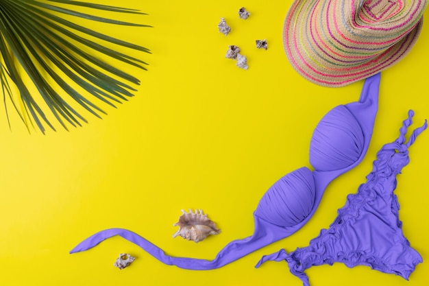 Bikini swimsuit with tropical palm's leaves on a yellow background. top view of woman's swimwear and beach accessories with copy space