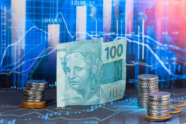 Bill of 100 reais brazilian money on a financial market graphic