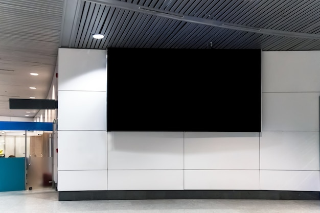 Billboard or advertising poster in the airport for advertisement concept background. a large black screen on a white wall in the waiting room train station, bus terminal. billboard in a public place