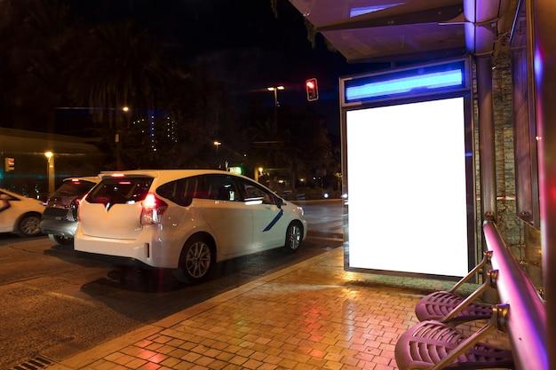 도시의 밤에 택시 승강장에 광고판