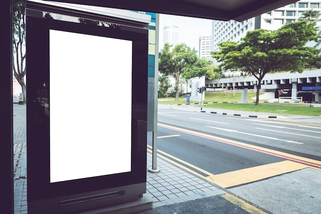 Billboard on bus stop with empty advertising banner on sunlit street.
