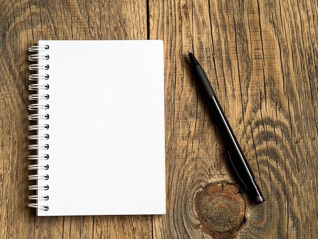メモと鉛筆のための空白のシートとビルボードは、抽象的な空の木製の背景。ノート