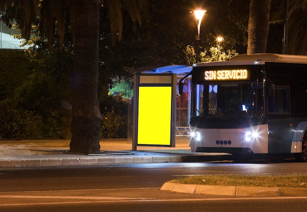 Billboard with light in the city center at night with bus text no service