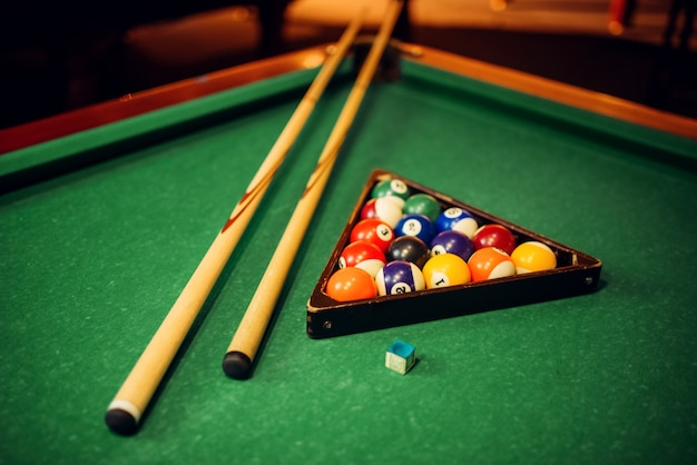 Billiard balls, cue and pyramid on green table