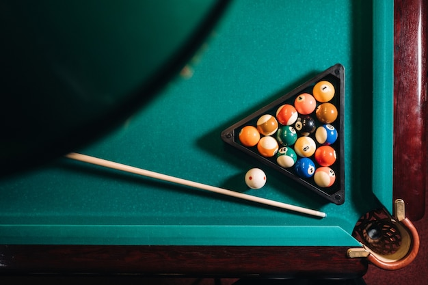 緑の表面とビリヤードクラブのボールとビリヤードテーブル。プールゲーム。