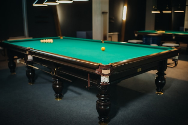 Billiard table with green surface and balls in the billiard club.