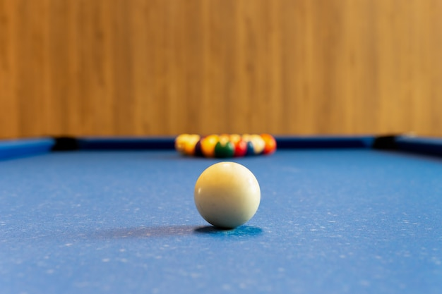 Billiards pool game. white ball on spot with set colours ball in background on blue table.