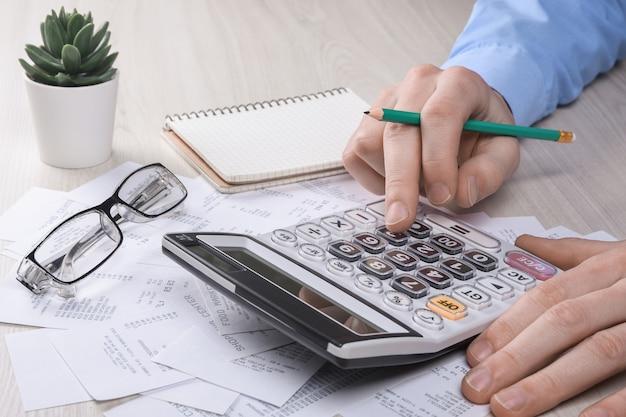 小切手付きの請求書と電卓。オフィスのテーブルで請求書を計算するための計算機。コストの計算。