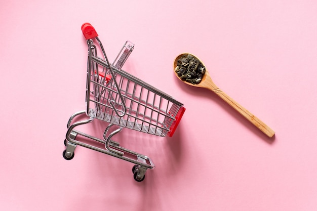 Biluochun and  shopping cart trolley.  chinese leaf green tea in a spoon on a pink background.