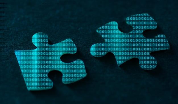Двоичный код на двух частях головоломки на черном фоне.