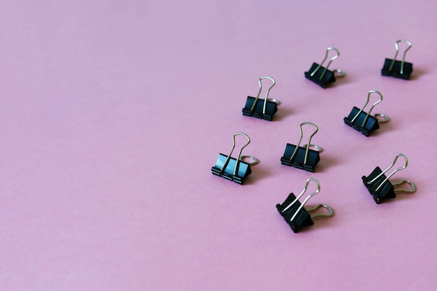 Binder clips on pink table
