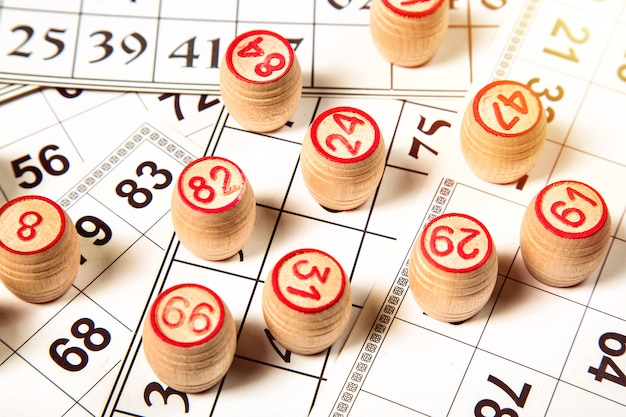 Bingo or lotto game, wooden kegs of lotto on cards,